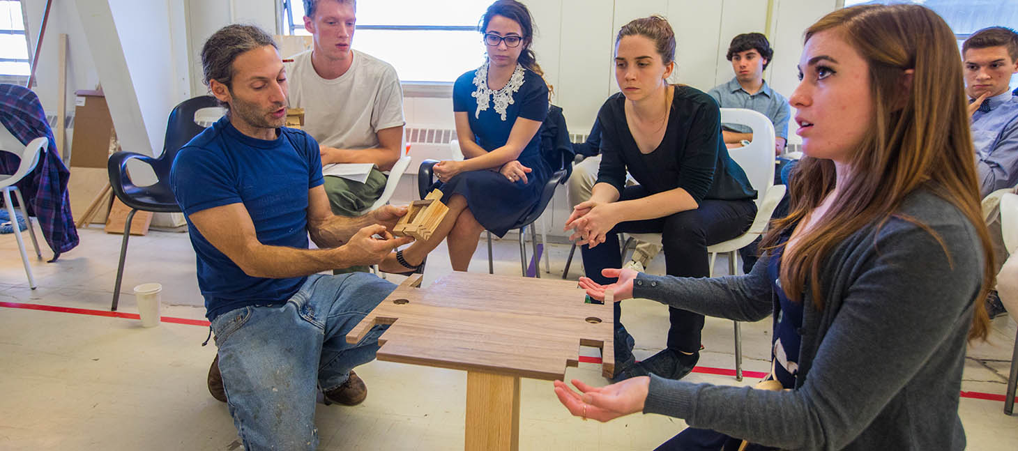 Architecture students examining a wooden base