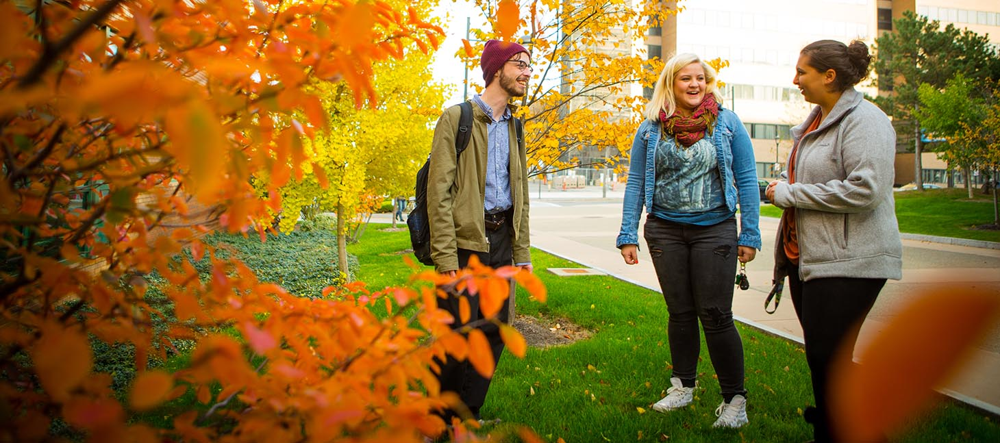 Three students talking outside on a fall day