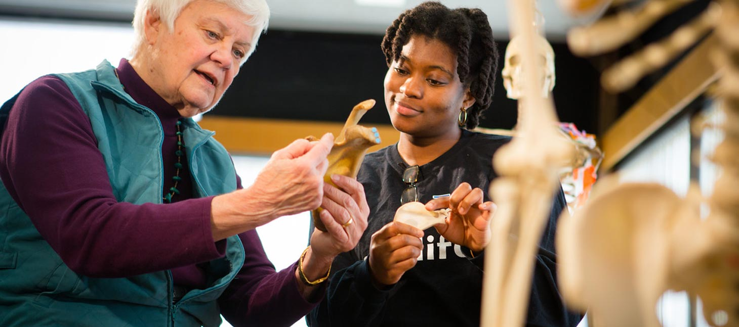 Student examining a bone with a professor