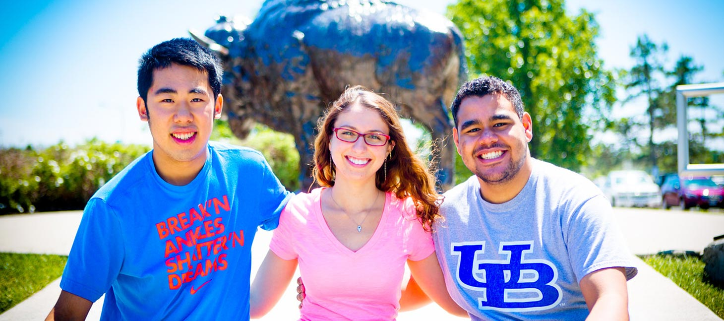 Students posing in front of a buffalo statue on campus