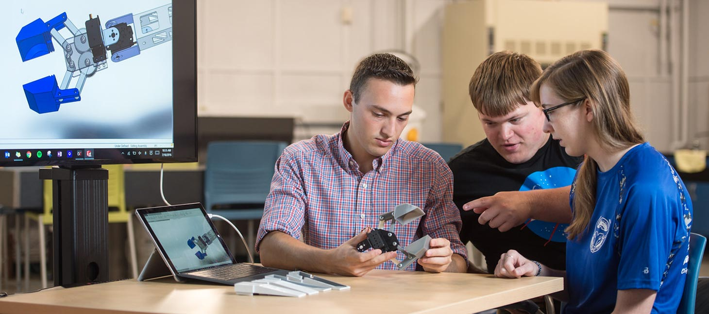 Engineering Students looking at a robotic arm